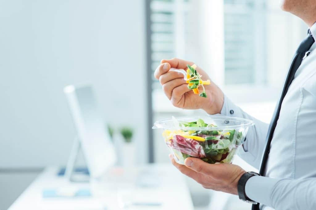 Un homme d'affaire entrain de manger une salade